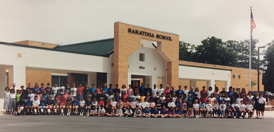 Color group photograph, taken in 1992, showing Saratoga's entire sixth grade class posing in front of the main entrance to the school.
