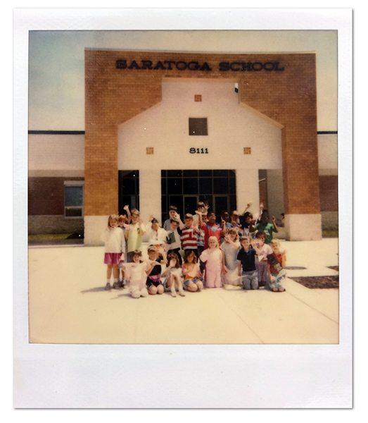 Color Polaroid photograph of the front entrance of Saratoga Elementary School taken in 1990. A group of approximately 23 students are sitting and standing together, waving at the camera.